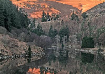Garreg-ddu Reservoir, with Esgair Penygarreg lit by late afternoon sun.